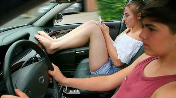 Kid driving without seat belts, with teen girl passenger resting her feet on the dash