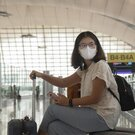 A woman in an airport with a suitcase and a mask