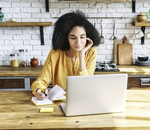 A woman sits at a laptop
