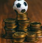 A toy football sits on top of a pile of cash