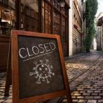 A closed coronavirus sign on a cobbled street