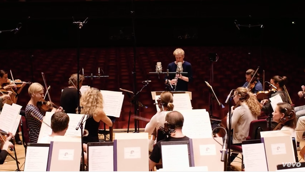 Photo of Martin Frost performing while conducting an orchestra